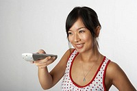 Woman holding remote control, smiling