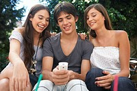 Teenage boy (14-16) holding camera phone, between two young women