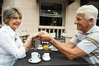 Senior couple sitting at outdoor cafe holding hands, smiling