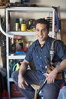 Portrait of a young man holding a tool belt