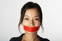 Woman with red tape over mouth, portrait