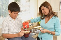 Mother pouring milk into her son´s cereal bowl