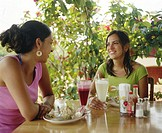 Young women talking at cafe table