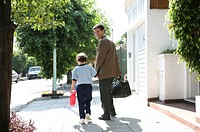 Father walking with son (6-8) smiling, outdoors