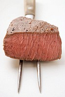 Beef steak, a piece cut off, on meat fork