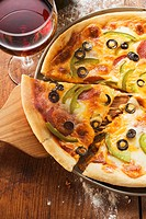 Pizza with cheese, salami, peppers & olives, glass of red wine
