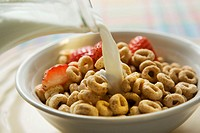 Pouring milk over cereal in a bowl 1