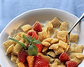 A dish of cereal flakes, strawberries and raspberries