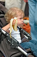 Babyboy eating banana in stroller