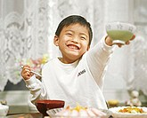 Japanese boy holding a rice bowl in his outstretched hand