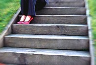 young business woman sitting on wooden stairway
