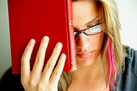 20 yr old young woman holding red book on forehead