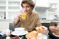 Portrait of a young man sitting at the breakfast table