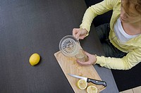 High angle view of a young woman pouring orange juice from a juicer into a glass