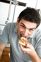Portrait of a young man eating a slice of pizza