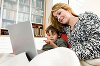Side profile of a mother sitting with her son and using a laptop