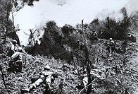 U.S. Marines aim their rifles at the entrance to a cave after hurling an explosive charge to force out Japanese troops hiding on Okinawa, main island ...