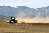 Farm tractor disking a field in Camas County, Idaho. Disking is a process of evening off plowed ground.