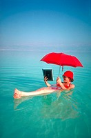 Woman reading a book and holding an umbrella while afloat in the Dead Sea.