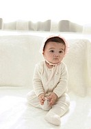 Close-up of a baby girl sitting on a bed