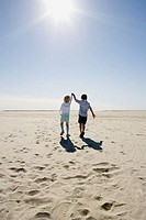 Boy and girl walking on beach holding hands