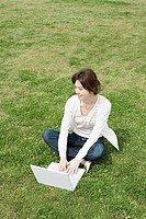 Woman using laptop in the park