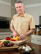Man cutting vegetables in kitchen