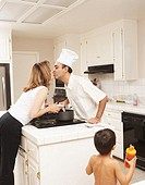 Family in kitchen, husband kissing wife, son (2-4) holding bottle