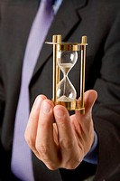 Businessman holding hourglass, mid section (focus on hourglass)
