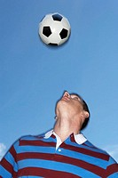 Man playing soccer, looking up at ball, close-up (blurred motion)