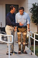 Man walking with leg braces, second man assisting