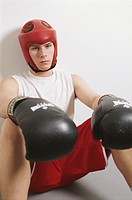 Teenage male boxer (15-17) sitting on floor, portrait
