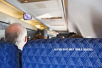 Man sitting in commercial airline, rear view