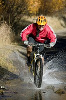 Man riding mountain bike through puddle
