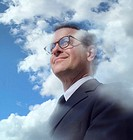 Mature businessman with head in clouds (Digital Composite)