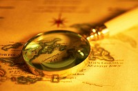 Magnifying glass on antique map, close-up