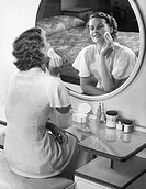 Woman applying powder with powder puff in front of mirror, (B&W)