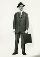 Businessman standing in studio, (B&W), portrait