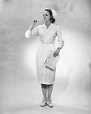 Young woman in nurse gown, checking temperature on thermometer, (B&W)