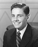Teenage boy (16-17) in full suit, smiling, (B&W), portrait