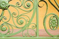 Detail of green painted decorative iron railing in front of yellow wall, Charleston, South Carolina