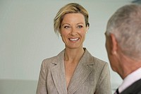 Young business woman smiling, back of the head of elderly man