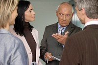 Elderly manager in a meeting with three business people, gesturing with one hand