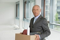 Elderly manager carrying a cardboard box, standing in an empty office