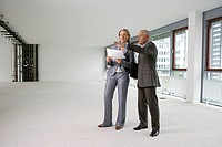 Elderly manager standing next to business woman in an empty office, pointing at something