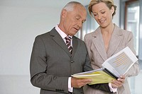 Elderly manager and business woman taking a look at business papers, both smiling