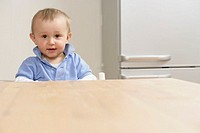 Baby boy sitting at table and looking at camera