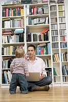 Father with a laptop and a mobile phone sitting in front of a shelf, son standing in front of him