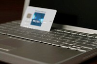 Credit card sticking between the keys of a laptop (part of), close-up