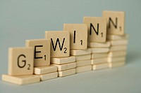 Word build with single wooden tokens, selective focus